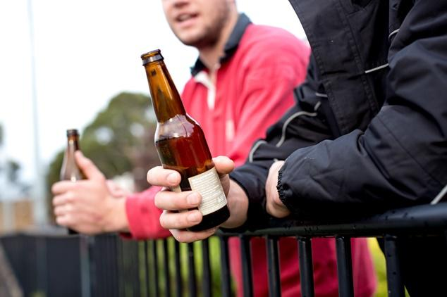 Close up of two beer bottles, each held by a different person leaning on a metal fence.