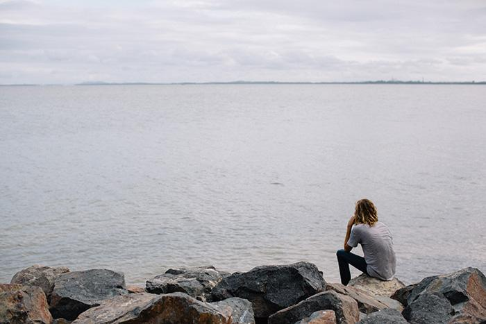 Lone person sat atop ocean-side rocks