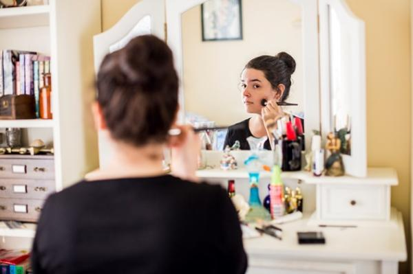 Young person applies make up in front of drawer-top mirror