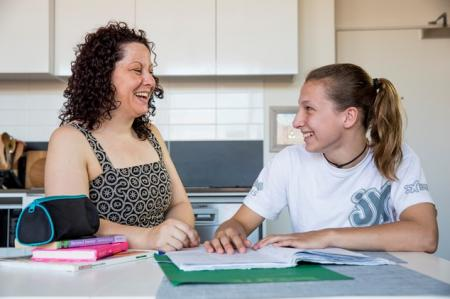 Young person and parent sit together at kitchen table with exercise book and pencil case.